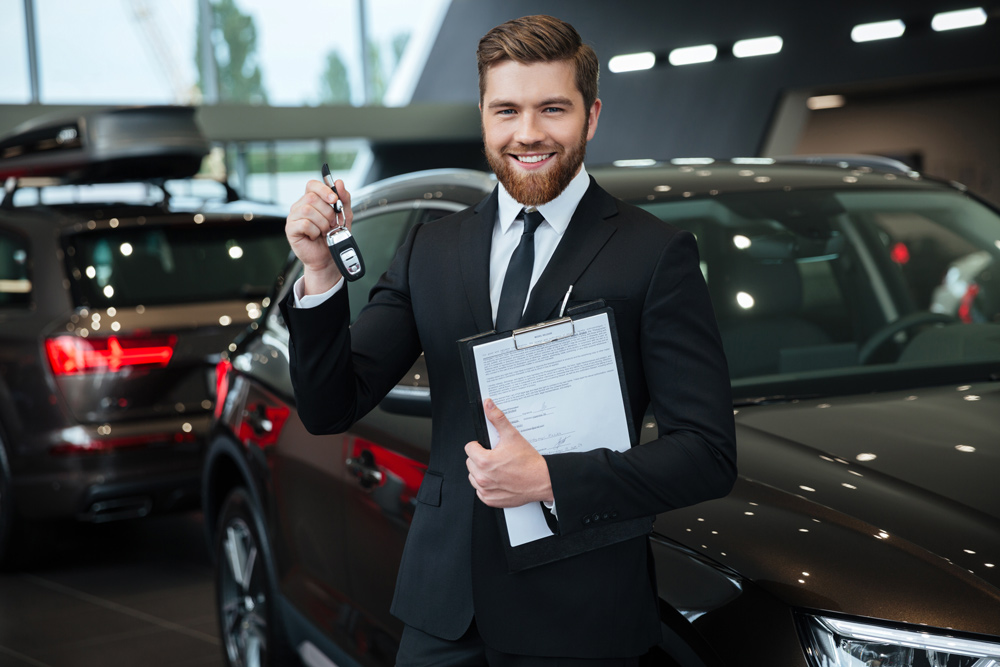 male car salesman holding a key in a car dealership